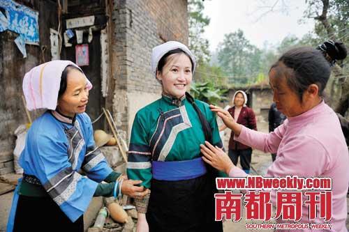 贵州六枝特区郎岱镇,穿青人为李芊墨试穿穿青族的服装。