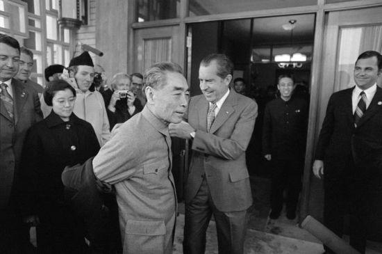 1972年2月24日,中国,北京:美国总统尼克松帮助周恩来总理脱外套。美国总统尼克松正式访华。2月28日,中美两国发表了指导两国关系的《中美联合公报》,中美交往的大门终于被打开。尼克松此次访华是0世纪国际外交史上最重大的事件之一。