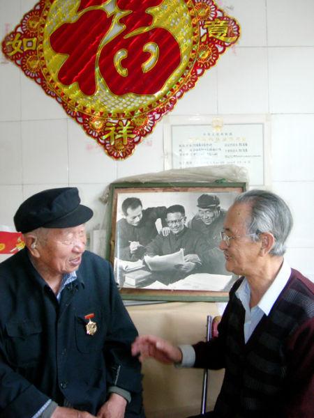 梁昭乃和陈有唐,背后是他们年轻时和同事的合影。中国周刊记者/宋合营 摄