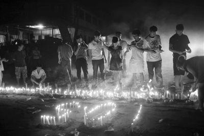 10月16日晚,船员们在关累码头岸边,点燃蜡烛祭奠死难者。