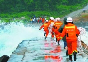 紧急施救 8月7日,消防队员携带绳索,冒险通过堤坝冲上小岛。