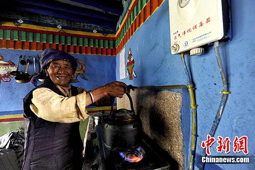 西藏山南地区贡嘎县吉雄镇溜琼村的农民索朗宁杰正在用沼气烧水。