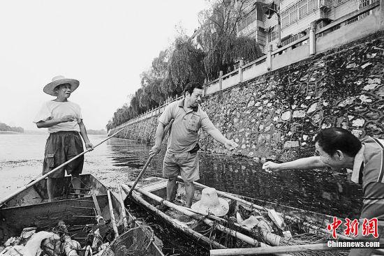 """他每天的工作非常""""简单"""",就是驾着一艘小船在河中清理河中的垃圾和水草。"""