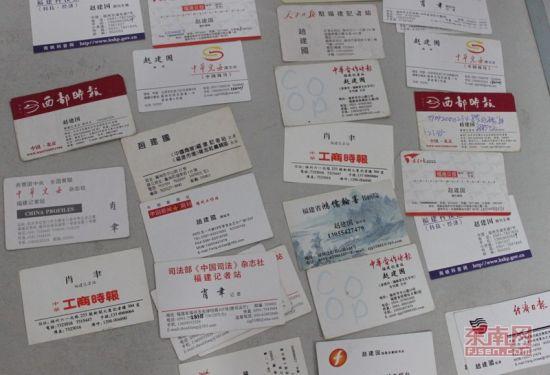"""赵某冒充多家媒体记者印制的名片,多张化名""""肖聿"""""""