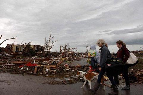 5月21日,在美国俄克拉何马州穆尔市,当地居民走过被龙卷风摧毁的房屋废墟。新华社发(宋穹摄)