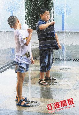 """两个小男孩借用喷泉""""洗澡""""(图片来源:江淮晨报)"""