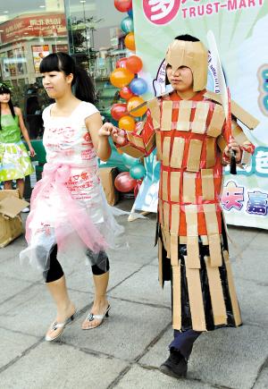 3月26日,大学生志愿者在活动中展示用废旧物品制作的服装,宣传废物