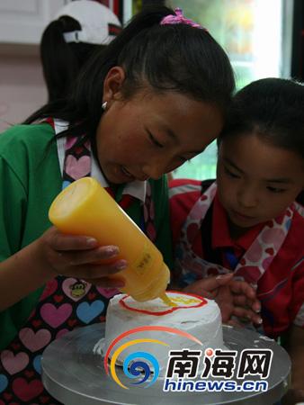 看着蛋糕胚,孩子开心的笑了(南海网记者 杨婷婷摄)   南海网5月16日消息(南海网记者杨婷婷)15日下午,来自玉树灾区的20名孩子,参观完海南省博物馆后,兴致勃勃的来到海口上帮百汇城爱侬浓蛋糕店,与来自海口的20名爱心家庭的孩子们一起DIY制作蛋糕。两个孩子亲手制作的小蛋糕,融入了两个民族孩子们的友谊和感情。   首先,爱侬浓蛋糕店首先为孩子们穿上了事先准备好的可爱的花眼围裙,穿上了围裙的孩子们还真是像模像样,真像位糕点师傅呢!蛋糕店的师傅首先将先烤好的蛋糕胚放在孩子们的面前,然后告诉他们制作蛋糕的步骤