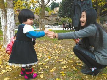 南门坝生态公园里,银杏树下嬉戏的小孩和家人.