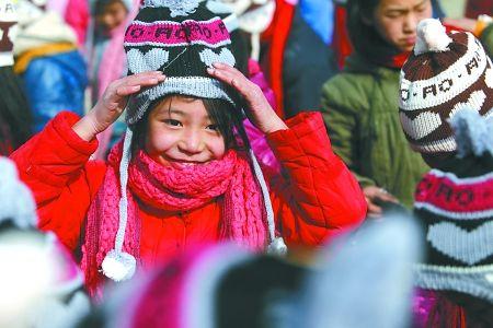 12月22日,彭水县联合乡石柱小学,戴上爱心织物的孩子开心地笑起来.