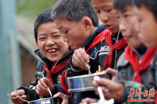 """沙坝小学的孩子们开心的吃着""""免费午餐""""。"""