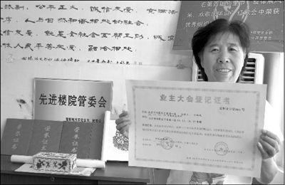"""于家园一区业委会主任展示北京首个""""业主大会登记证书""""。 本报记者 张淑玲 摄"""