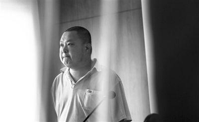 被告人紧闭双唇眼中含泪站在法庭上。昨日,廖丹因涉嫌诈骗罪在法院受审,后获准回家照顾妻子。新京报记者 王贵彬 摄