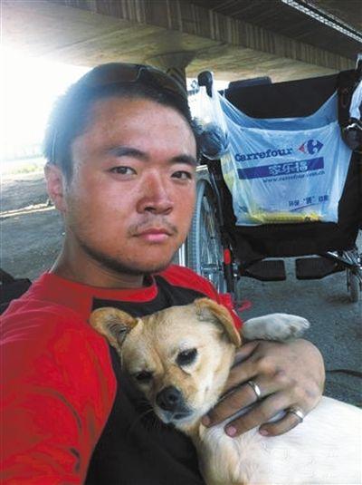 """北京小伙樊蒙和小狗""""蝴蝶""""在旅途中合影。他准备推着母亲、牵着小狗徒步前往西双版纳。"""