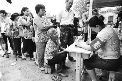 昨日,青龙湖镇北车营村,受灾村民登记领取方便面、矿泉水等救灾物资。新京报记者 尹亚飞 摄