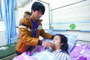昨日,16岁弟弟罗红刚在医院照料受伤的姐姐罗红萍。重庆晨报记者 胡杰 摄