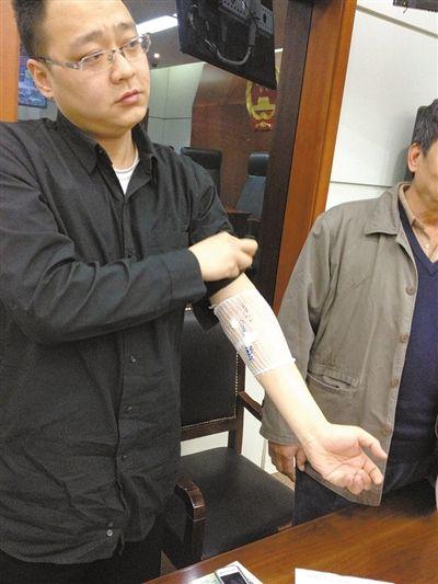 李先生(左)展示胳膊上的治疗痕迹。昨日,李先生认为家具甲醛超标,导致自己患上白血病,将销售方告上法庭。新京报记者 刘洋 摄