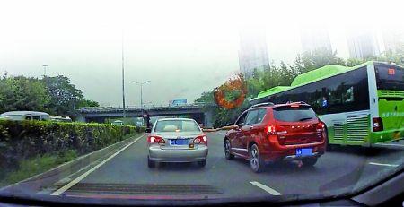 """网友""""嘿高兴""""的行车记录仪拍下的惊险一幕。从图片中可以看到,左边车辆的乘员探出身体,与右边车辆的司机似乎交接了某个物品。"""