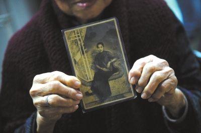 90岁黄月蓉为记者介绍当年在新加坡当妈姐时拍下的照片