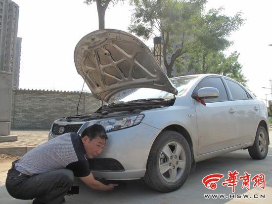 """昨日下午,商洛市丹凤县的彭全斌说,自己的车辆在汽修厂修理期间再次""""被肇事"""",他正在查看自己的车辆受损情况。华商报记者 陈永辉 摄"""