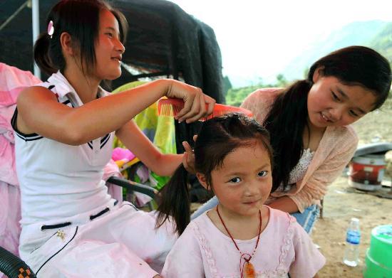图文:志愿者在青川县的帐篷里为小女孩梳头