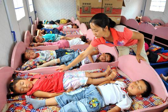 图文:夏艳老师在看护午休的幼儿园小朋友