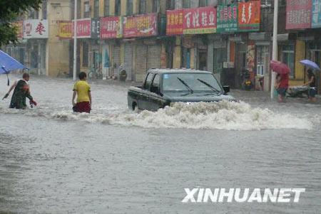 组图:河北沧州遭暴雨商店门前搭木板挡水
