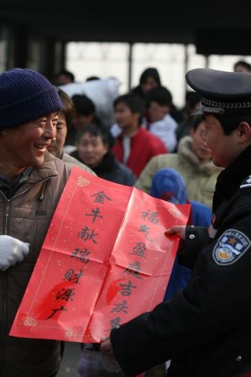 图文:民警在阜阳火车站为农民工送上春联