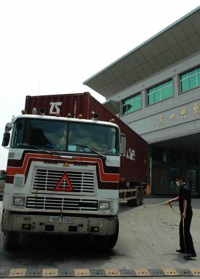 图文:广西东兴口岸工作人员在给车辆消毒