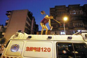 摊贩爬上急救车顶挥铁铲与城管对峙(组图)