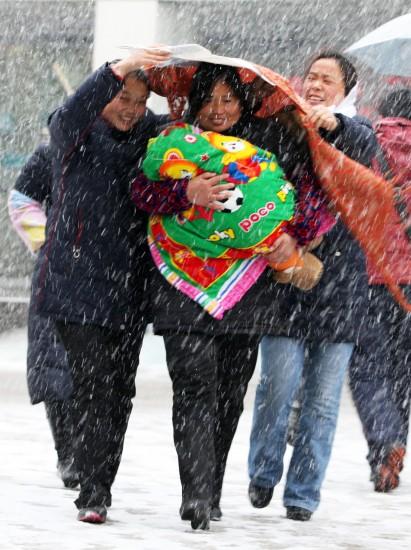 图文:妇女使出浑身解数为孩子遮风挡雪