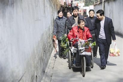 輪椅邊圍滿了人,大家有說有笑,場面十分溫馨