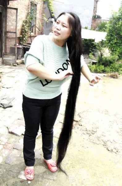 为准确测量头发长度,纪双双站在椅子上,大姐纪丽丽和邻居捋着她的头发图片