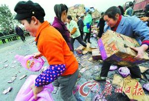 高速公路附近的村民哄抢散落地上的货物。CFP供图