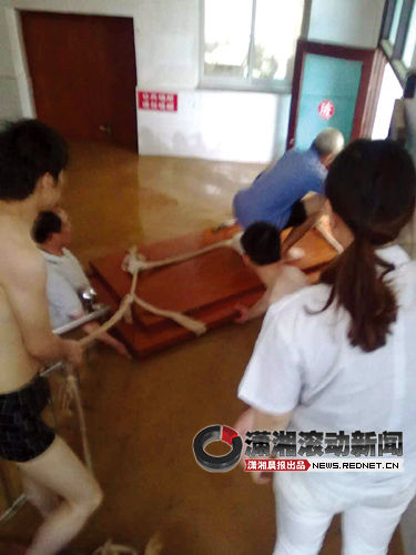 余坪乡中心卫生院,村民与护士用木板转移病人。 图/潇湘晨报读者提供