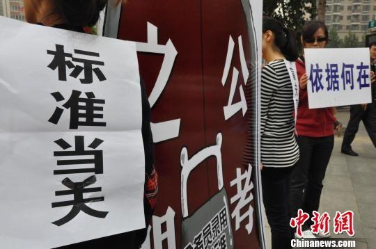 """10月15日,郑州市3名热心公益的女大学生在广场上演了名为""""标准当关,盲夫莫开""""的行为艺术。 周小云 摄"""