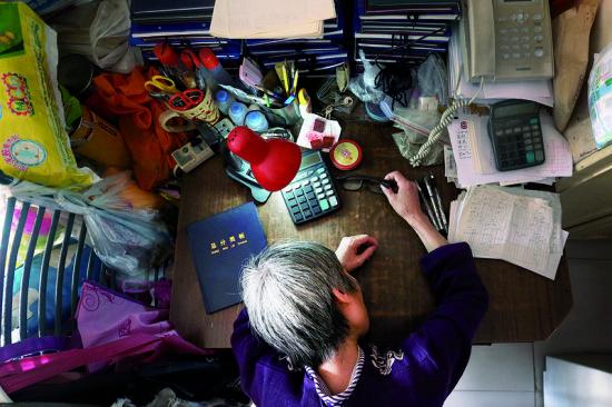 通宵忙碌的郭敏趴在桌上小憩,她说自己想工作到70岁 摄/法制晚报记者 洪煜