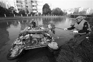 """海曙区推行""""河长制"""",环卫工人在清理庙后河河岸上的垃圾"""