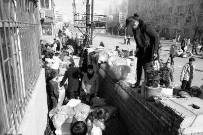 13日,涉事学校学生翻墙搬行李。图/东方IC