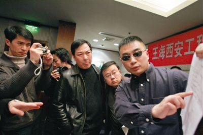 2005年2月28日,戴着一副标志性墨镜的王海现身西安某酒店召开新闻发布会。图/CFP