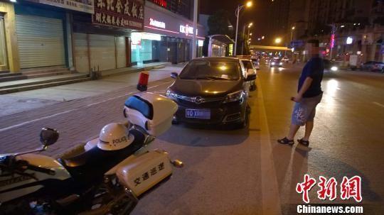 """6月4日晚,南宁青林路一辆私人车被协警""""贴单"""",其先后是开来吃宵夜的警车。 王刚 摄"""