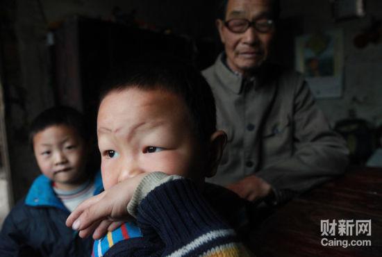毛坪村的小男孩袁石(中),告诉记者,他的妹妹袁丽一岁的时候,被抢走了,至今下落不明。他想念妹妹,多次梦到她回家了。  财新记者 李漠 摄