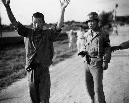 1950年7月21日,一位韩国军人押送一位朝鲜俘虏前往战俘营.