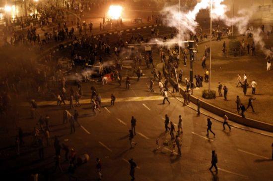1月28日,在埃及首都开罗,人们在解放广场游行时与警方发生冲突。当日,埃及首都开罗爆发骚乱,数万名示威游行者与警方对峙后占领解放广场,人们扔燃烧弹,焚烧街头物品,与警方发生冲突,警方开枪并发射催泪弹。 新华社记者才扬摄