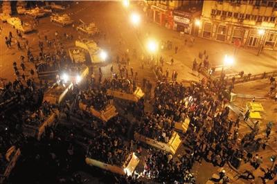 1月29日凌晨,在埃及首都开罗,示威者爬上装甲车。新华社发