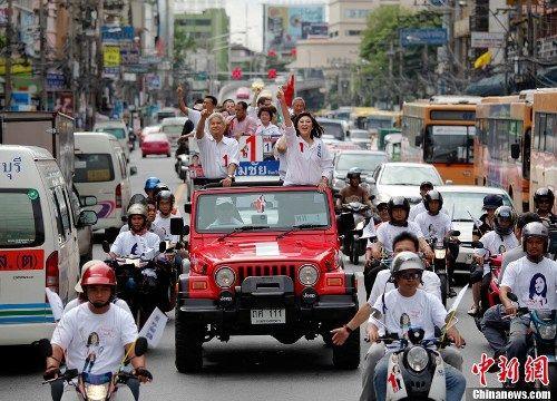 图为7月2日,阿披实对手,泰国前总理他信的妹妹英禄在曼谷乘车向支持者挥手致意。