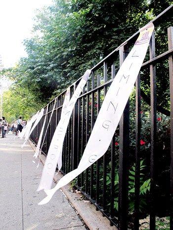 一条条白丝带引来了过路民众和游客的注意,许多人在此驻足。侨报记者李�f摄
