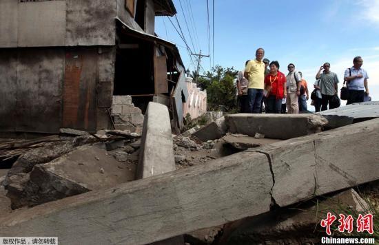 图为2月8日,菲律宾总统阿基诺三世(穿黄色衣服者)在一栋被毁的建筑前视察。