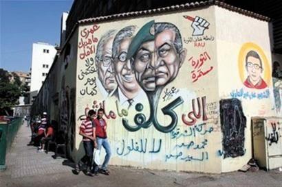 两名埃及青年经过解放广场前的涂鸦,涂鸦上的头像分别为穆巴拉克、埃及武装部队最高委员会主席侯赛因・坦塔维、在总统选举首轮中败选的阿姆鲁・穆萨以及总统候选人艾哈迈德・沙菲克