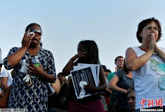 当地时间7月20日,爆发严重枪击案的美国丹佛世纪奥罗拉影院周边500米范围被警方用警戒线封锁,蜂拥而至的媒体抢占影院停车场空地进行现场报道。中新社发 王欢 摄